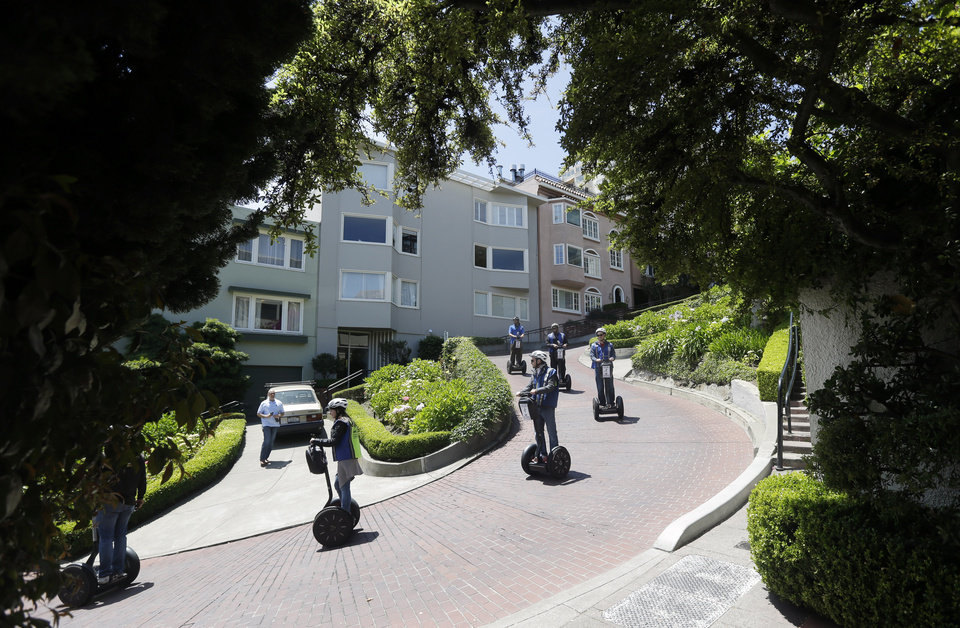 Photo - A group goes down Lombard Street on segways on Tuesday, May 20, 2014, in San Francisco.  San Francisco's crooked street could soon be closed to tourists in the summertime. A transportation commission is scheduled to consider an experimental shutdown of the famously curvaceous block of Lombard Street plus an adjoining block where cars line up and wait.(AP Photo/Marcio Jose Sanchez)