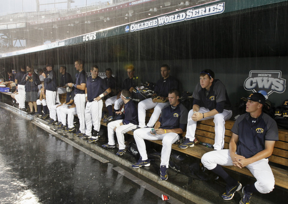 Photo -   Kent State players wait in the dugout as heavy rain drenches pregame warmups before an NCAA College World Series elimination baseball game against South Carolina in Omaha, Neb., Wednesday, June 20, 2012. (AP Photo/Nati Harnik)