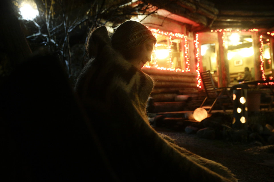 Photo - A guest sits on a bench in the outdoor sauna area at the British Banya bathhouse, Saturday, Feb. 15, 2014, in Krasnaya Polyana, Russia. The banya is an institution in Russia, where bathhouse traditions date back for centuries. (AP Photo/Jae C. Hong)