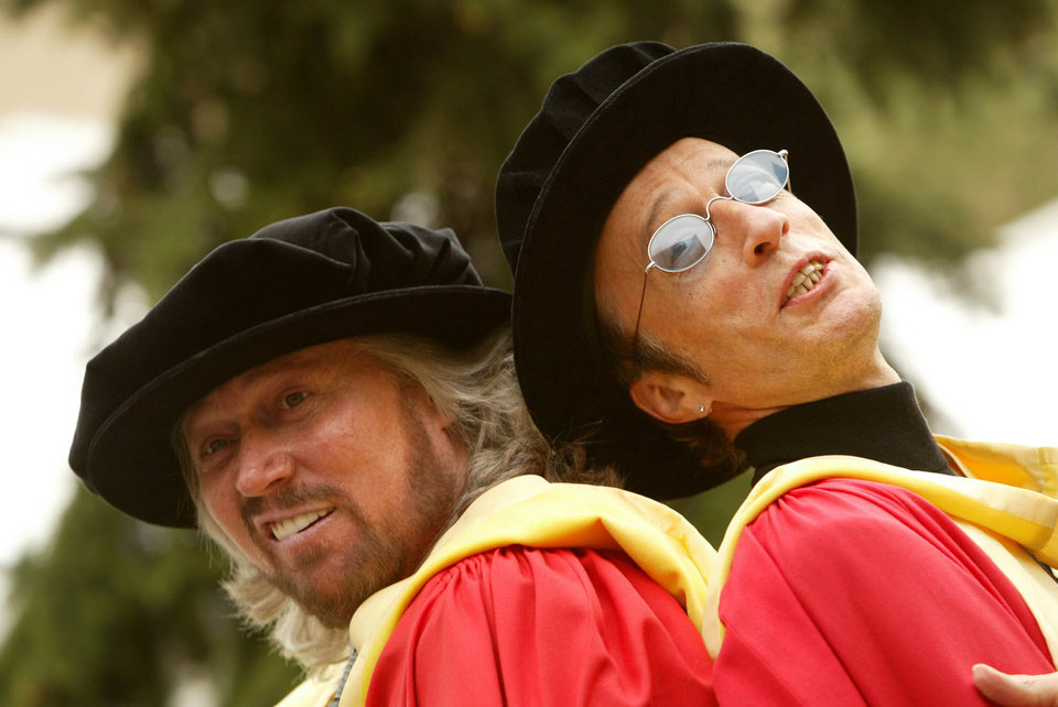 Photo -   In this Wednesday, May 12, 2004, file photo, Barry Gibb, left, and Robin Gibb, right, clown around as they pose for pictures after receiving honorary degrees from the University of Manchester, in Manchester, England, Wednesday May 12, 2004. A representative said on Sunday, May 20, 2012, that Robin Gibb died at the age of 62. (AP Photo/Jon Super)