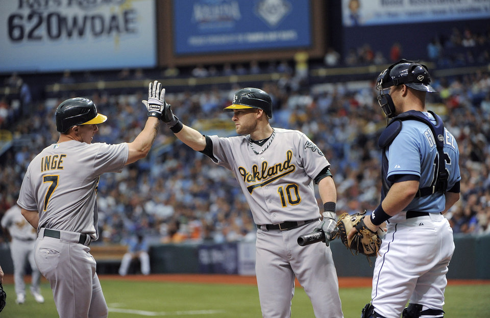 Photo -   Oakland Athletics' Brandon Inge, left, celebrates his three-run home run with Daric Barton, center, as Tampa Bay Rays catcher Chris Gimenez watches during the third inning of a baseball game Sunday, May 6, 2012, in St. Petersburg, Fla. (AP Photo/Brian Blanco)