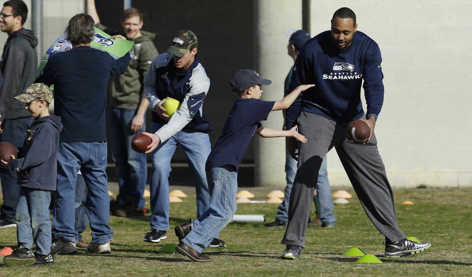 Photo - Seattle Seahawks  linebacker K.J. Wright, right, and Bryan Walters, third from right, hand off  footballs to kids Monday, March 31, 2014, at a community gathering in Darrington, Wash. The NFL football players and other team officials visited Darrington to lend support to the town, which is located near the site of the deadly mudslide that hit the community of Oso,Wash. on March 22, 2014. (AP Photo/Ted S. Warren)