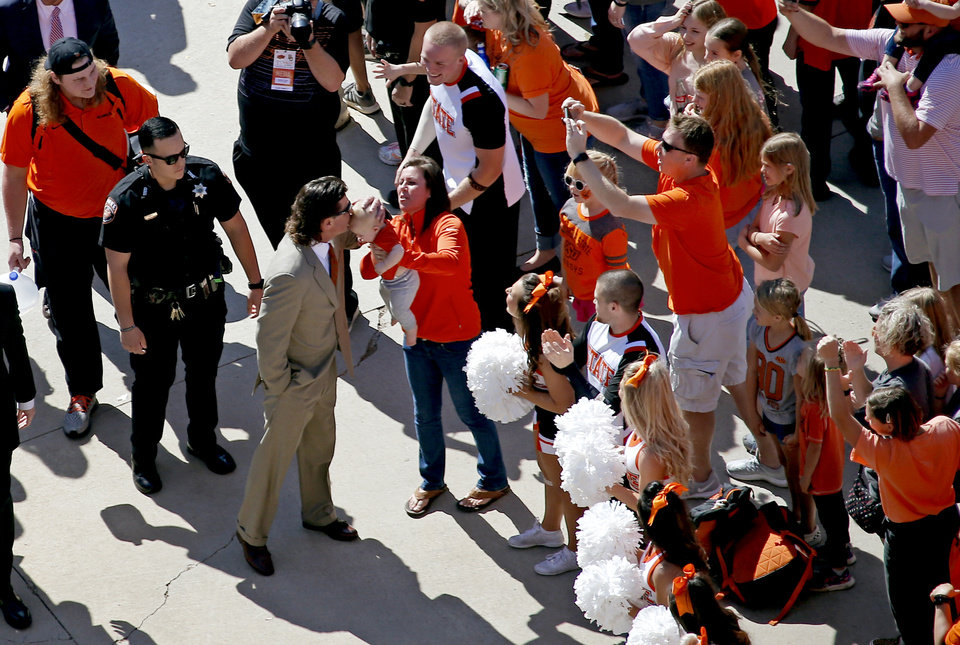 Photo - Oklahoma State head coach Mike Gundy kisses a baby during the Spirit Walk before the college football game between Oklahoma State University and Baylor at Boone Pickens Stadium in Stillwater, Okla., Saturday, Oct. 19, 2019. [Sarah Phipps/The Oklahoman]