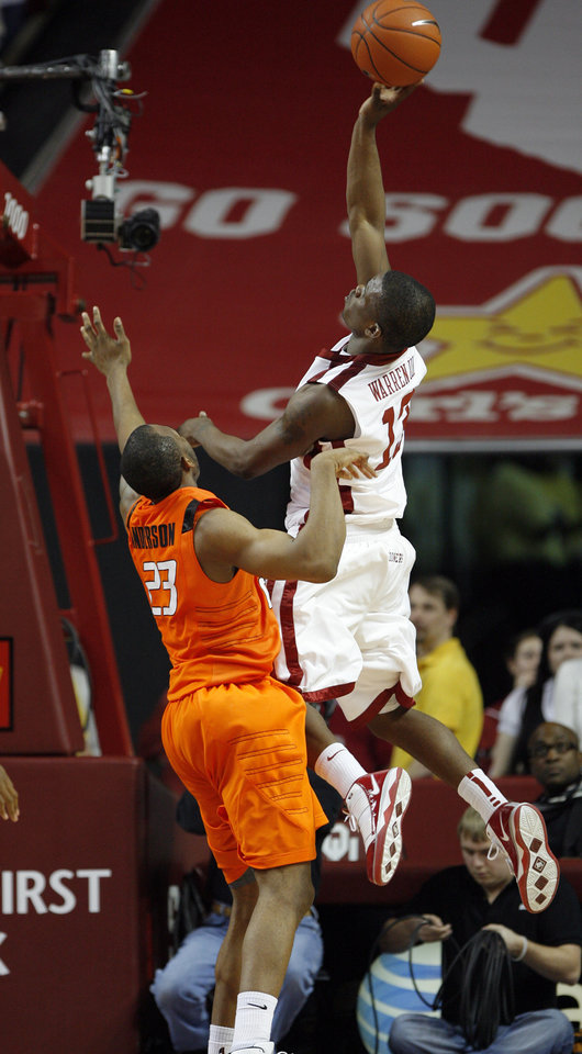Photo - Willie Warren (13) shoots over James Anderson (23) during the second half of the college bedlam basketball game in which The University of Oklahoma Sooners (OU) defeated Oklahoma State University University Cowboys (OSU) 62-57 in overtime at the Lloyd Noble Center on Monday, Jan. 11, 2010, in Norman, Okla.