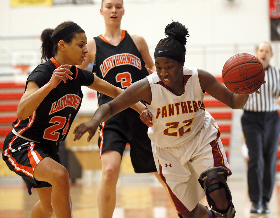 Photo - Da'Jah Coffey (22) of Putnam City North drives the ball against MiKayla Alexander (24) of Booker T. Washington as MaKenzie Ellis (3) looks on during the championship game of the Lady Jag Classic girls basketball tournament between Booker T. Washington and Putnam City North at Westmoore High School in Oklahoma City, Saturday, Jan. 12, 2013. Photo by Nate Billings, The Oklahoman