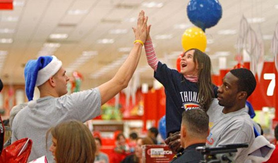 Photo -  Oklahoma City Thunder player Cole Aldrich, left, high-fives with Emily Appelbaum, 6, in the arms of Jeff Green during a shopping spree with the Sunbeam Family Services Grandparents Raising Grandkids program and the Thunder at a Target store in Oklahoma City, Thursday, December 16, 2010.  Photo by Bryan Terry, The Oklahoman