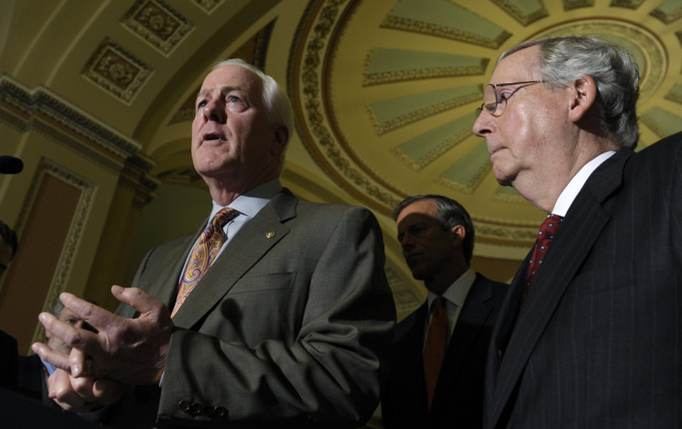 Photo - Senate Minority Leader Mitch McConnell of Ky., listens at right as Senate Minority Whip John Cornyn of Texas, left, speaks to reporters on Capitol Hill in Washington, Tuesday, Oct. 1, 2013, following a policy luncheon. Lawmakers on Capitol Hill continue to scramble to reach agreement on funding the federal government.  (AP Photo/Susan Walsh)