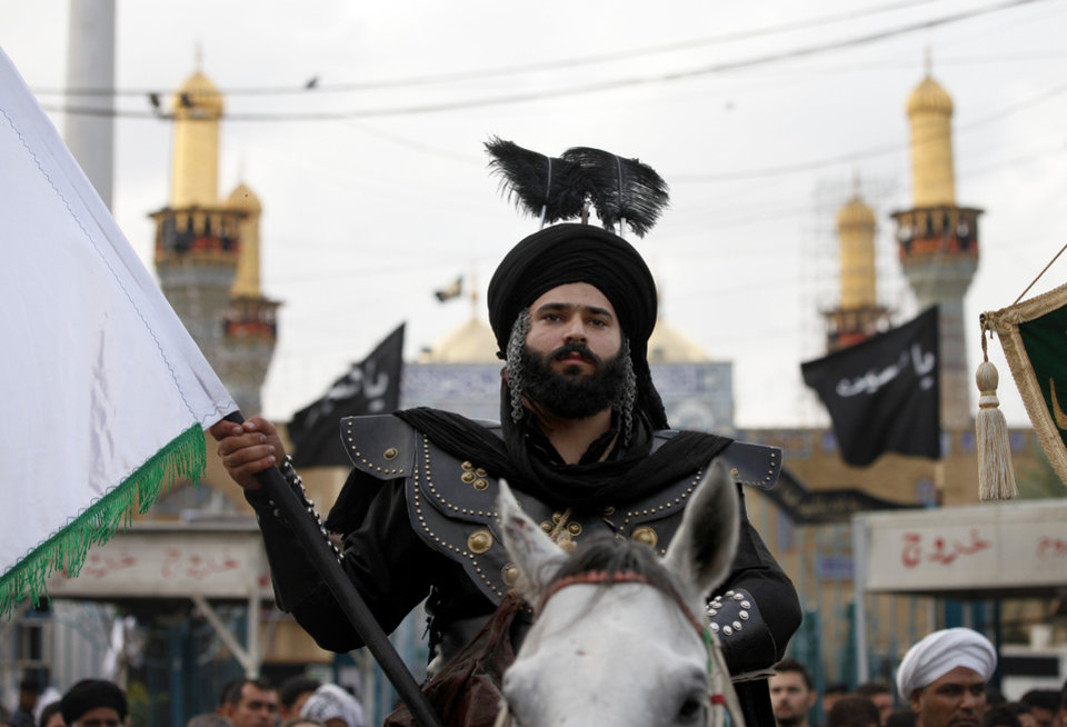 A man playing the role of Imam Abbas, brother of Imam Hussein, rides on horseback at the Imam Moussa al-Kadhim shrine during the festival of Ashoura in Baghdad, Iraq,Saturday, Nov 24, 2012. Ashoura marks the anniversary of the Battle of Karbala when Imam Hussein, a grandson of Prophet Muhammad, was killed. (AP Photo/Karim Kadim)