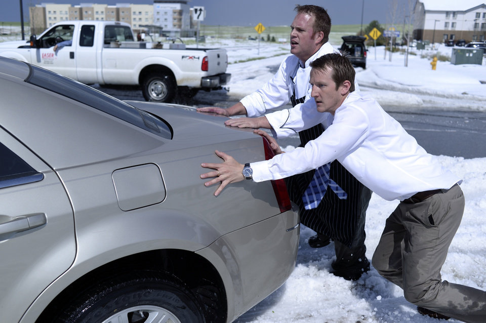 Photo - Chris Collins, left, and Paul Nellis, right, pushed a motorist out of the median on Tower Road Wednesday afternoon May 21, 2014. Hail piled more than a foot high on Tower Road stranded several vehicles following a storm that had both heavy rain and hail.  Both men work at the Embassy Suites hotel near the airport. (AP Photo/The Denver Post, Karl Gehring)