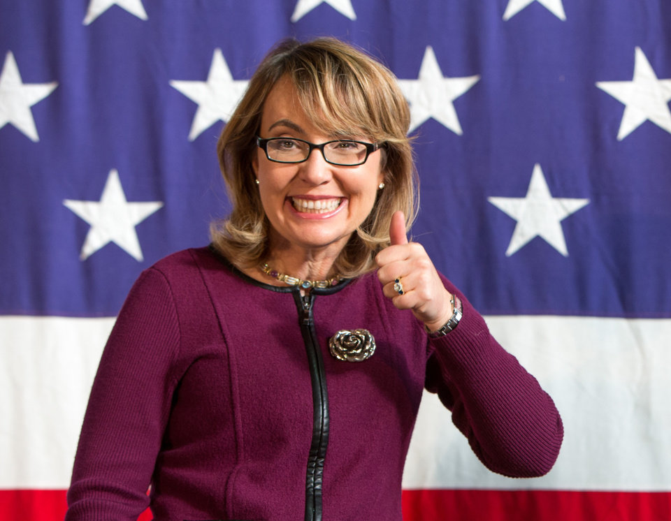 Photo - FILE - This Oct. 27, 2013 file photo shows former U.S. Rep. Gabby Giffords (D-Ariz.), at a fundraiser for U.S. Senate candidate Bruce Braley during the Bruce Blues & BBQ at the Iowa State Fairgrounds in Des Moines, Iowa. Giffords is working on a book about gun control. The Arizona Democrat and her husband, the retired Navy captain and astronaut Mark Kelly, are collaborating on
