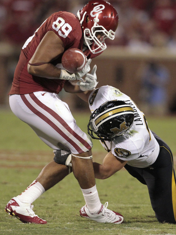 Photo - Oklahoma's Austin Haywood (89) juggles a  pass but holds on while being hit by Missouri's Luke Lambert (33)  during their game Saturday in Norman. OU won 38-28. Photo by Steve Sisney, The Oklahoman