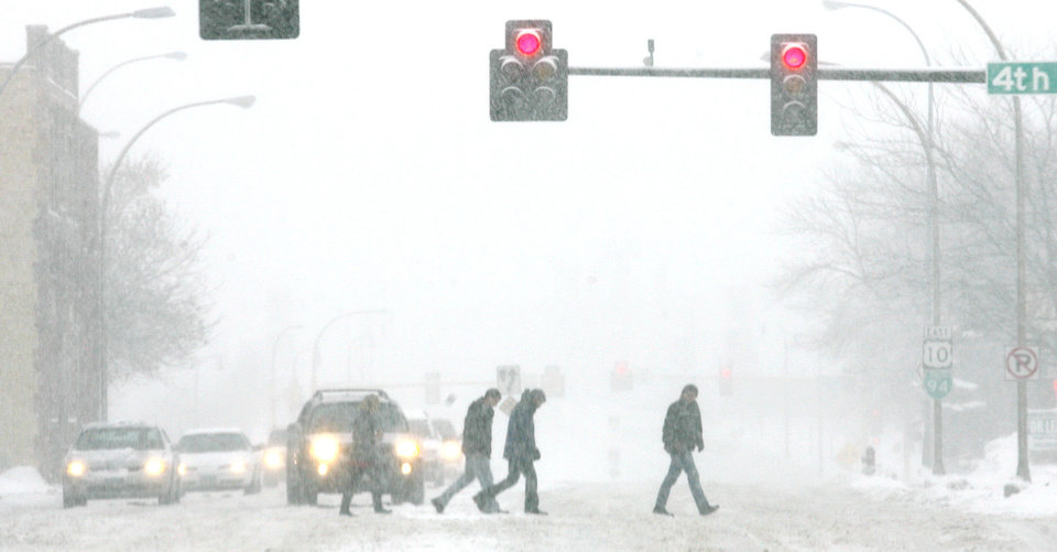 Photo - In this  Sunday, Feb. 10, 2013 photo pedestrians cross snow covered Main Avenue in downtown Fargo, N.D.  Blizzard warnings posted by the National Weather Service continued into Monday morning in central and northeastern South Dakota and southeastern North Dakota as the region began digging out from a blizzard that broke several longstanding weather records. (AP Photo/The Forum, Carrie Snyder)