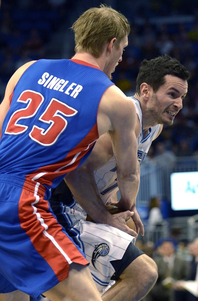 Photo - Orlando Magic guard J.J. Redick, right, is tied up by Detroit Pistons guard Kyle Singler (25) for a jump ball during the first half of an NBA basketball game in Orlando, Fla., Sunday, Jan. 27, 2013. (AP Photo/Phelan M. Ebenhack)