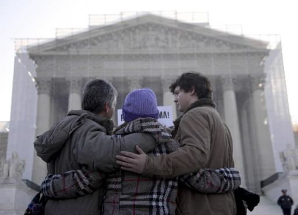 Photo - A group from Alabama prays in front of the Supreme Court in Washington, Wednesday, March 27, 2013, before the court's hearing on the Defense of Marriage Act (DOMA). In the second of back-to-back gay marriage case, the Supreme Court is turning to a constitutional challenge to the law that prevents legally married gay Americans from collecting federal benefits generally available to straight married couples. (AP Photo/Carolyn Kaster)
