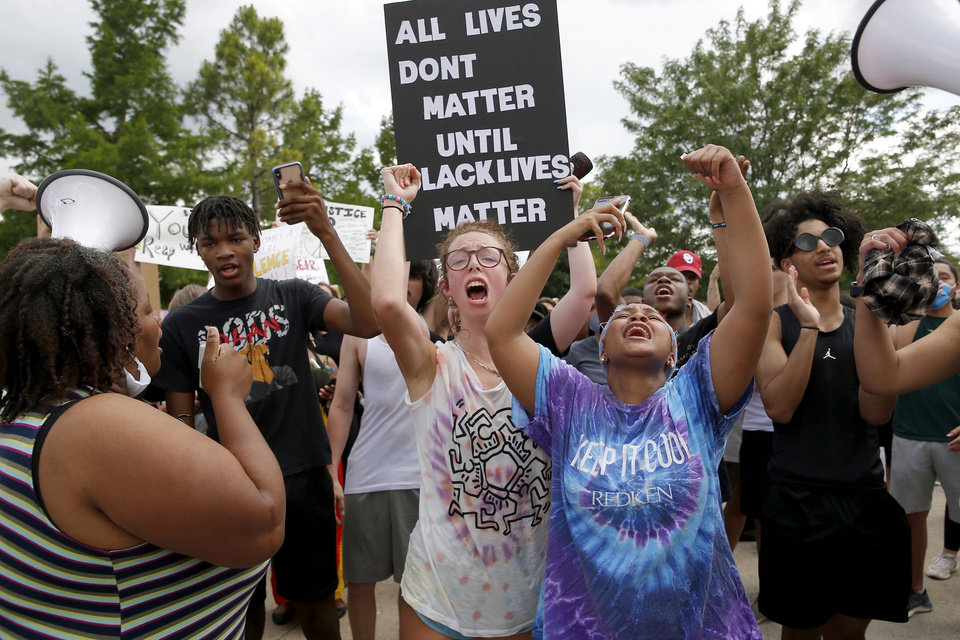 Photo - Protesters chant outside the Norman Police Department in Norman, Okla., Tuesday, June 2, 2020, in response to the death of George Floyd. [Sarah Phipps/The Oklahoman]