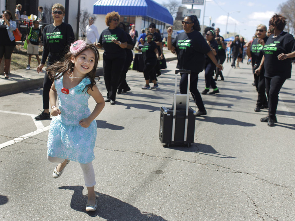 "Photo - Jesse Barton, 6, dances along with ""Oklahoma City's Original Line Dance Club"" performs at Open Streets OKC, along NW 23rd Street between Robinson and Western, Sunday, March 22, 2015. Photo by Doug Hoke, The Oklahoman"