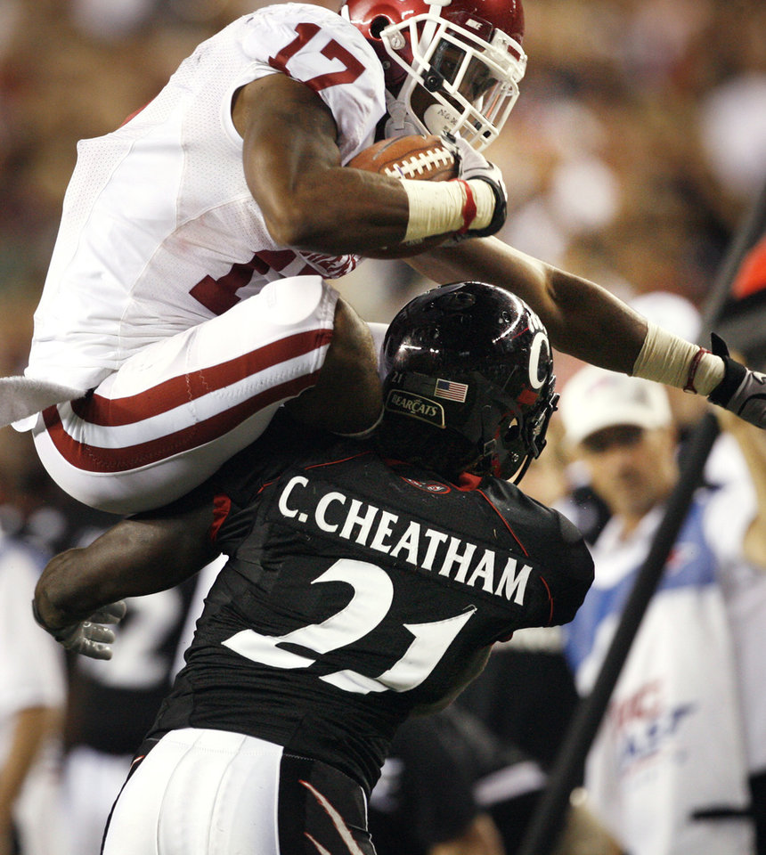 Photo - Mossis Madu (17) leaps over Camerron Cheatham (22) during the second half of the college football game between the University of Oklahoma Sooners (OU) and the University of Cincinnati Bearcats (UC) at Paul Brown Stadium on Saturday, Sept. 25, 2010, in Cincinnati, Ohio.   Photo by Steve Sisney, The Oklahoman