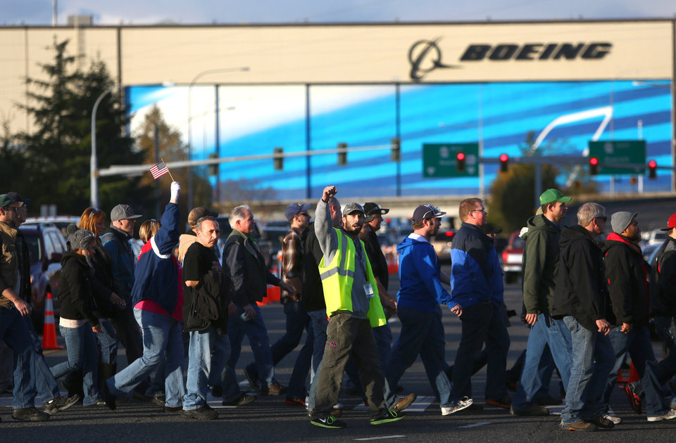 Photo - Boeing machinists march to cast their vote at the International Association of Machinists union hall in Everett, Wash. on Wednesday, Nov. 13, 2013. About 30,000 members of IAM District 751 voted on a contract extension that would cut pension and benefits in exchange for Boeing's commitment to build the 777X in Washington State. (AP Photo/seattlepi.com, Joshua Trujillo)  MAGS OUT; NO SALES; SEATTLE TIMES OUT; TV OUT; MANDATORY CREDIT