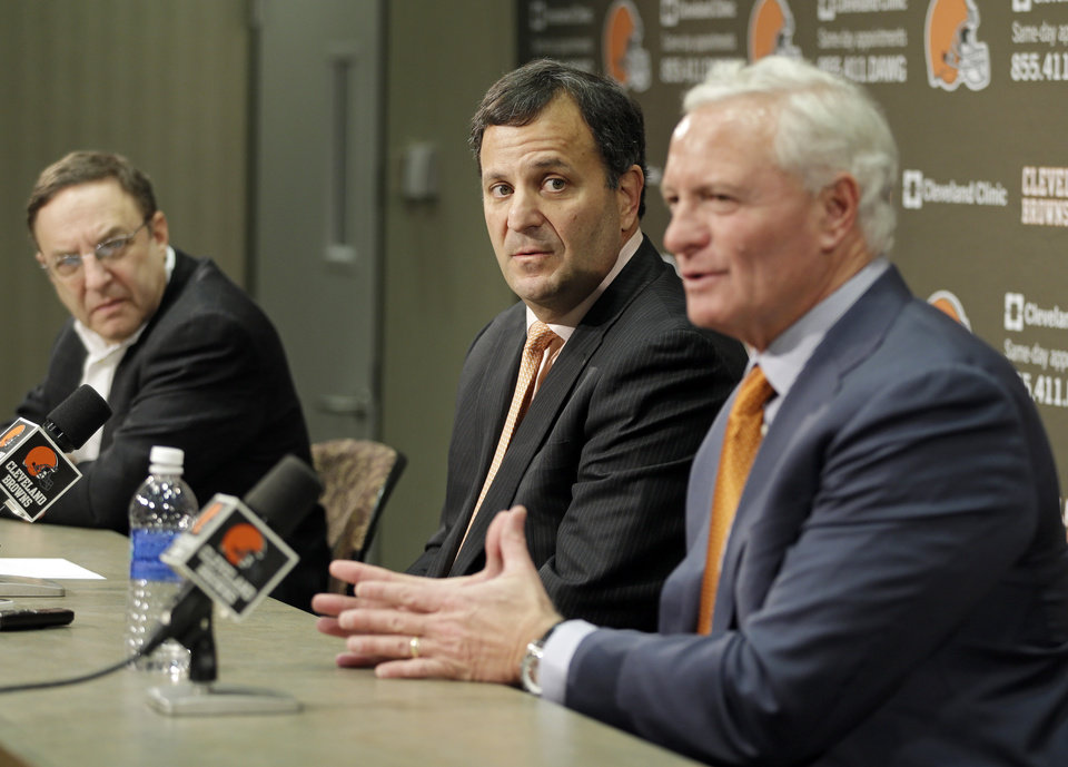 Photo - Mike Lombardi, center, the Cleveland Browns' vice president of player personnel, listens as owner Jimmy Haslam, right, speaks during a press conference at the NFL football team's practice facility in Berea, Ohio, Friday, Jan. 18, 2013. Browns' CEO Joe Bannler looks on, left. (AP Photo/Mark Duncan)