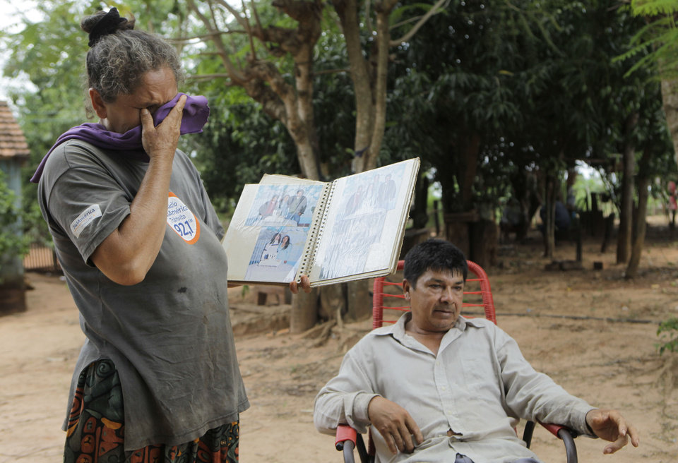 "In this Nov. 14, 2012 photo, Lidia Romero cries holding a family photo album as her husband Catalino Aguero talks in their home's yard in the Carro Cue settlement, near Curuguaty, Paraguay. The couple's son De Los Santos was killed and their daughter Lucia was imprisoned during the ""Massacre of Curuguaty"" on June 15 when negotiations between farmers occupying a rich politician's land ended with a barrage of bullets that killed 11 farmers and 6 police officers. ""They gave me my son's decomposing body in a black plastic bag. He had bullet wounds in both feet, but a huge hole in his neck,"" said Catalino Aguero.  (AP Photo/Jorge Saenz)"