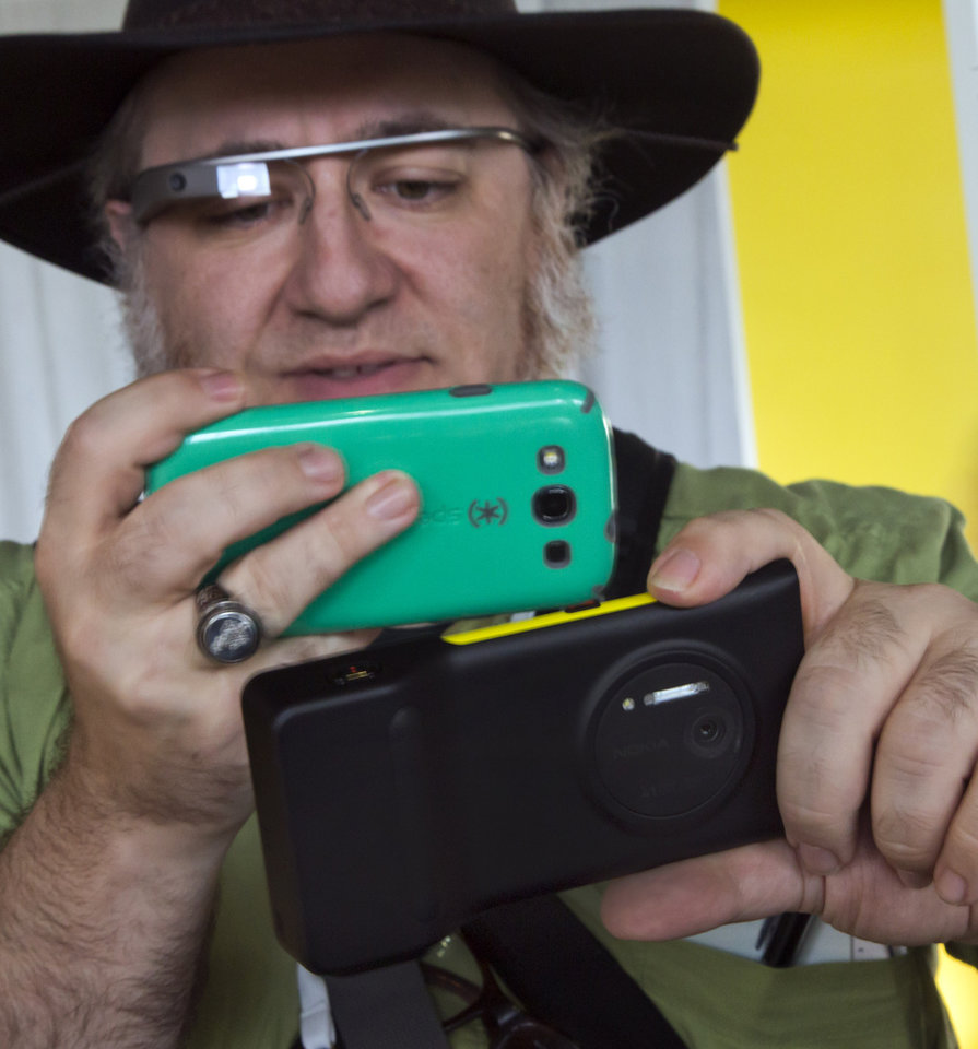Photo - Journalist Andy Inahtko, from Chicago, wearing Google Glass, uses a smartphone to photograph a Nokia Lumia 1020 at its introduction,  in New York,  Thursday, July 11, 2013. The Nokia Lumia 1020, with a 41-megapixel camera, records more detail than other camera phones and even tops point-and-shoot cameras. (AP Photo/Richard Drew)