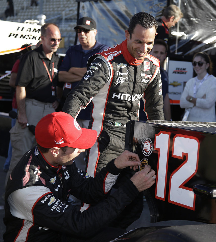 Photo - Will Power, left, of Australia, is greeted by teammate Helio Castroneves, of Brazil, after qualifying for the IndyCar auto race Saturday, Aug. 23, 2014, in Sonoma, Calif. Power won the pole position and Castroneves qualified in sixth. (AP Photo/Eric Risberg)