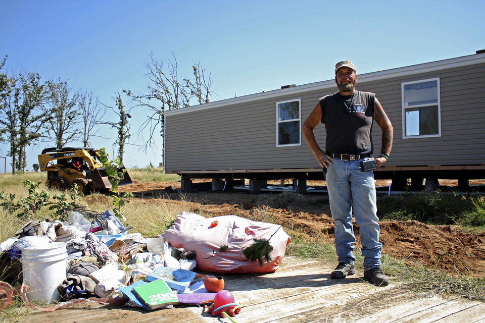 Photo - Stick Keiner stands on the foundation of a trailer home that was destroyed in the May 19th tornado. Behind him is a new trailer that his organization, US Defenders, was able to help get for a resident.  Adam Kemp