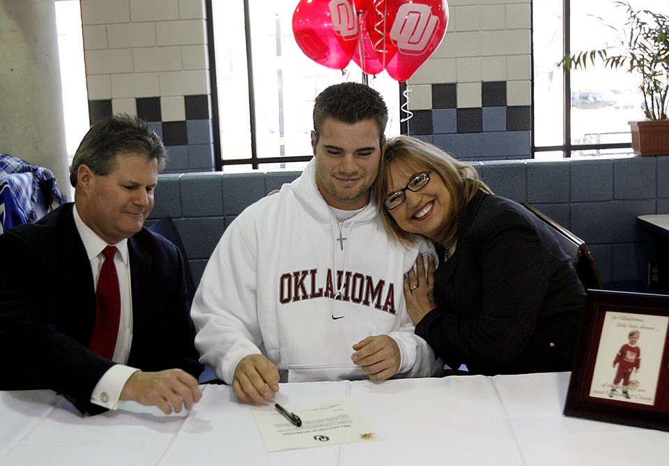 Photo - COLLEGE FOOTBALL LETTER OF INTENT SIGNING DAY, SIGN, OU, GAIL BOX, CRAIG BOX: Enid's Austin Box gets a hug from his mother Gail as his father Craig looks on after Box signed his letter of intent to play football with the University of Oklahoma on Wednesday, Feb. 7, 2007, in Enid, Okla.     by Chris Landsberger, The Oklahoman  ORG XMIT: KOD