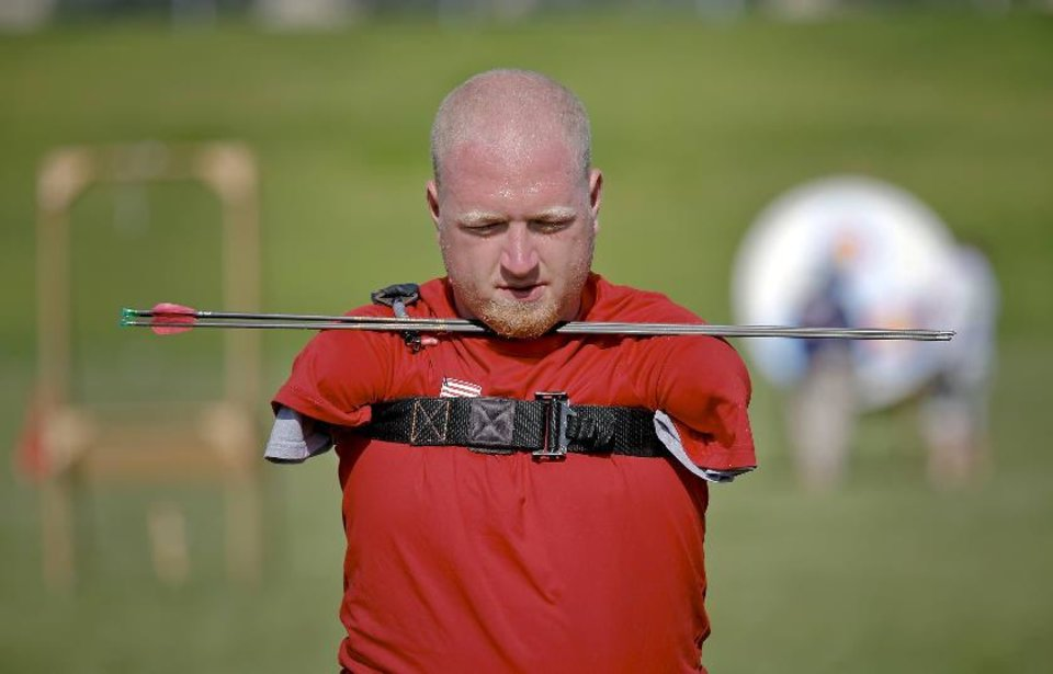 Photo - Matt Stutzman, known as the Armless Archer carries back his arrows as he takes part in the archery event during the Endeavor Games at the University of Central Oklahoma on Friday, June 7, 2013 in Edmond, Okla. Photo by Chris Landsberger, The Oklahoman