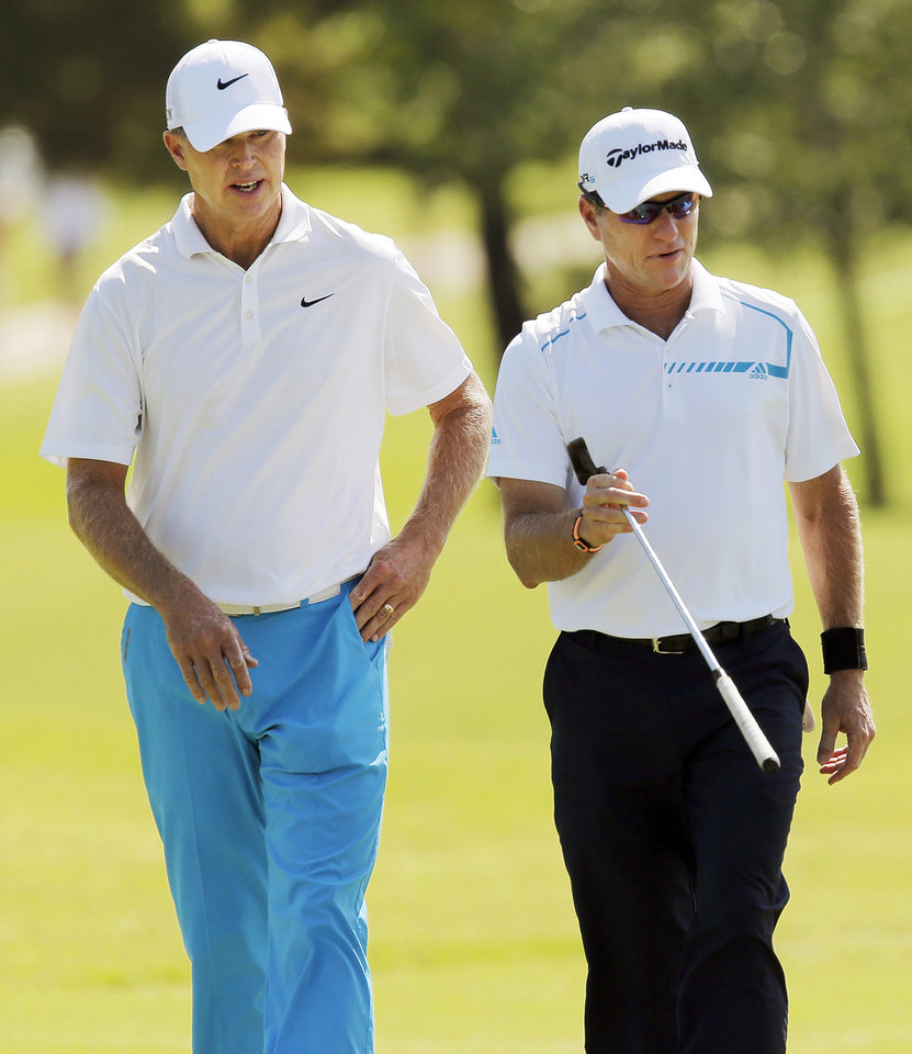 Photo - Bob Tway, left, and Scott Verplank talk as they walk to the No. 16 green during practice rounds for the U.S. Senior Open golf tournament at Oak Tree National in Edmond, Okla., Monday, July 7, 2014. Photo by Nate Billings, The Oklahoman