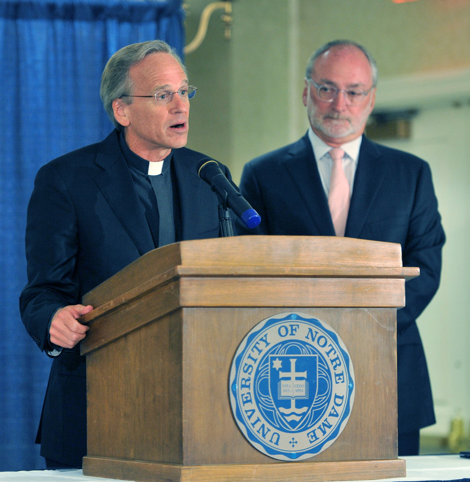 Photo - Rev. John I. Jenkins, C.S.C. the University's President, left,  talks about the academic scandal Friday Aug. 15, 2014 in South Bend, Ind. Notre Dame says it is investigating