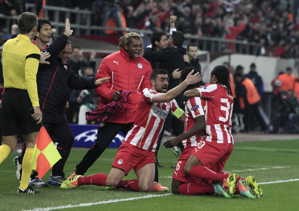 Photo - Olympiakos' Joel Campbell, center, celebrates with his teammates after scoring the second goal against Manchester United during their Champions League, round of 16, first leg soccer match at Georgios Karaiskakis stadium, in Piraeus port, near Athens, on Tuesday, Feb. 25, 2014. (AP Photo/Thanassis Stavrakis)