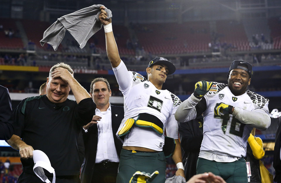 Photo - Oregon head coach Chip Kelly, left, Marcus Mariota, middle, and Michael Clay celebrate a win over Kansas State after the Fiesta Bowl NCAA college football game Thursday, Jan. 3, 2013, in Glendale, Ariz.  Oregon defeated Kansas State 35-17.(AP Photo/Ross D. Franklin)