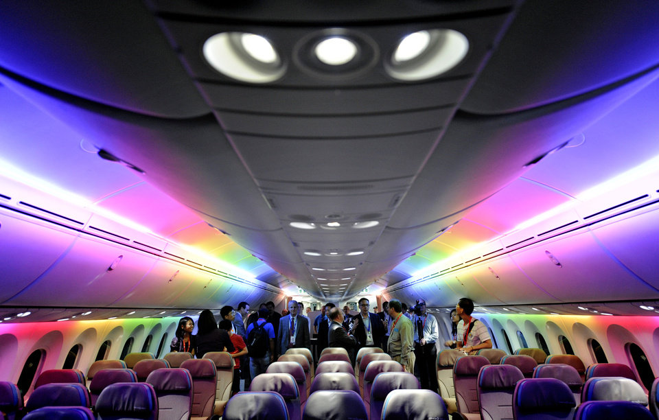 FILE - In this Feb. 12, 2012, file photo, members of the media tour Boeing 787 Dreamliner's cabin displaying versatile LED lighting system during a press preview in Singapore. While Boeing�s 787 Dreamliners are grounded, the batteries causing airliner�s troubles can still fly. At the time the government certified the 787 as safe, federal rules barred the type of batteries used to power the airliner�s electrical systems from being carried as cargo on passenger planes because of the fire risk. But new rules exempt aircraft batteries from the ban on large lithium ion batteries as cargo on flights by passenger planes. (AP Photo/Bryan van der Beek, File)