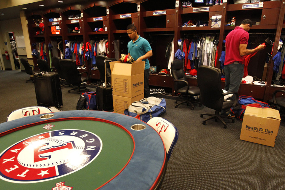 Texas Rangers catcher Luis Martinez, left, and relief pitcher Alexi Ogando, right, clear out their lockers in the team clubhouse Saturday Oct. 6, 2012, in Arlington, Texas. Manager Ron Washington was shocked and Josh Hamilton was getting booed. After two consecutive World Series, and twice getting within one strike of a title last year, the Rangers didn't even win a playoff game this time. (AP Photo/Tony Gutierrez)