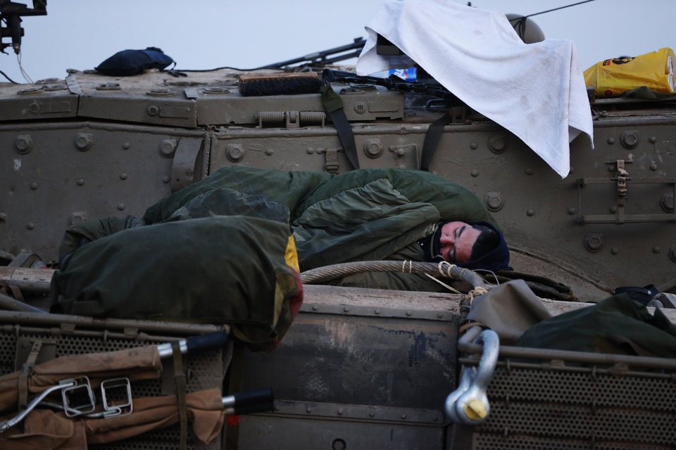 Photo -   An Israeli soldier sleeps on a tank at a staging area near the Israel Gaza Strip Border, southern Israel, early Tuesday, Nov. 20, 2012. On Tuesday, grieving Gazans were burying militants and civilians killed in ongoing Israeli airstrikes, and barrages of rockets from Gaza sent terrified Israelis scurrying to take cover. Efforts to end a week-old convulsion of Israeli-Palestinian violence drew in the world's top diplomats Tuesday, with U.S. President Barack Obama dispatching his secretary of state to the region on an emergency mission and the U.N. chief appealing from Cairo for an immediate cease-fire. (AP Photo/Lefteris Pitarakis)
