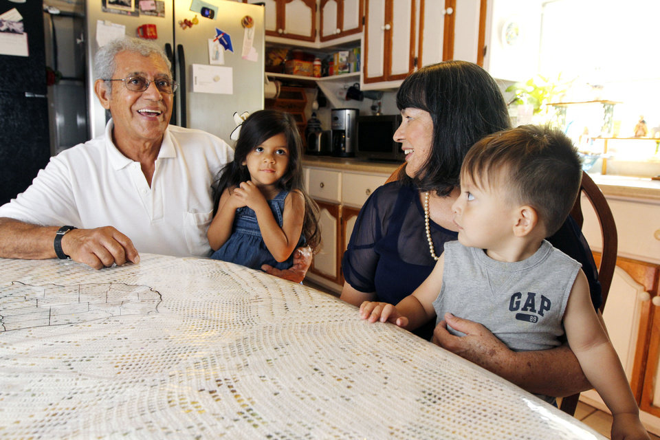 Photo - Elsa Garcia, a Latina breast cancer survivor, along with her husband, Roberto and grandchildren Yori, 4, and Ethan, 1, sit at the breakfast table at their home in Oklahoma City, OK, Friday.  PAUL HELLSTERN - Oklahoman
