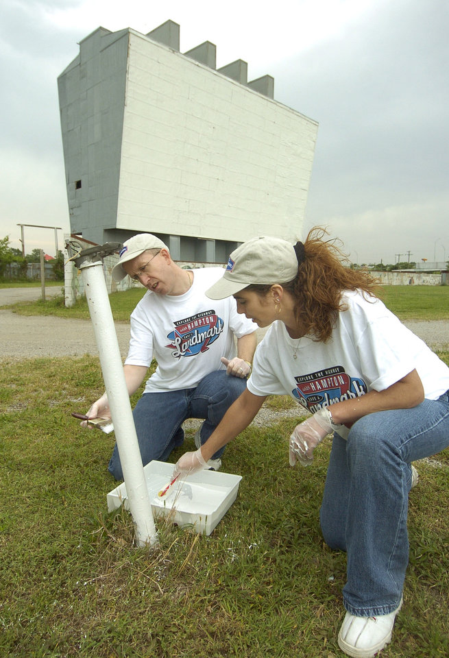 "Ron Murdock and Angel Leep paint one of the many old speaker poles at the Admiral Twin Drive-Inn Theater along old Route 66 as a part of the ""Save-A-Landmark"" program.  Tulsa, Okla. 05/24/05   By Paul Hellstern/The Oklahoman"