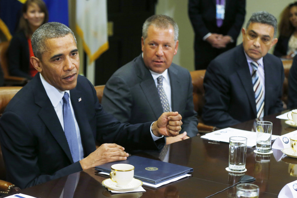 Photo - President Barack Obama meets with business leaders about creating and investing in jobs in the U.S., Tuesday, May 20, 2014, in the Roosevelt Room at the White House in Washington. From left are: the president; Joe Hinrichs, executive vice president and president of the Americas, Ford Motor Company; and Sanjay K. Jha, CEO, Globalfoundries. (AP Photo/Charles Dharapak)