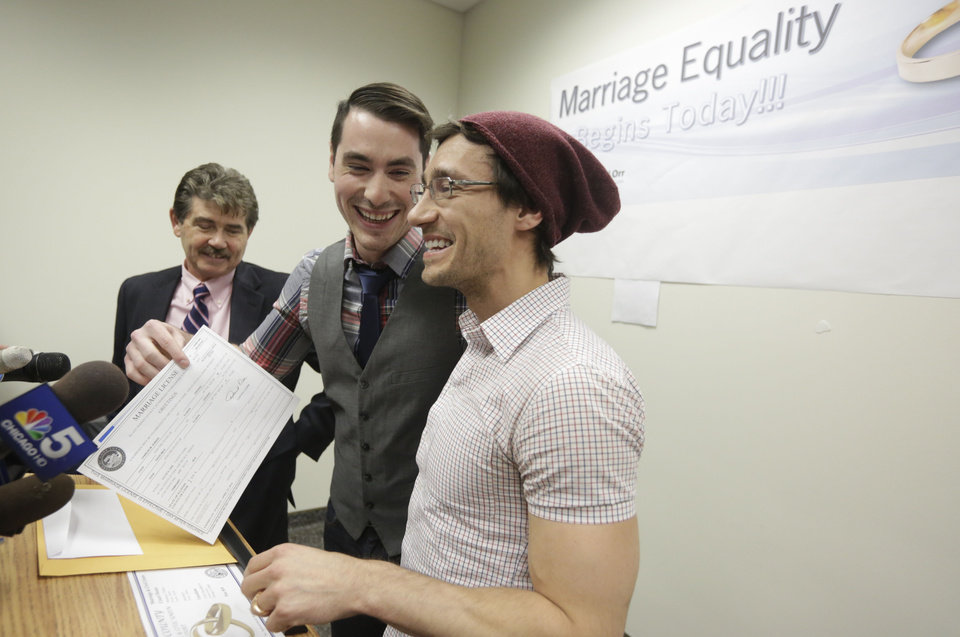 Photo - CORRECTS SPELLING TO WILK IN SECOND REFERENCE INSTEAD OF WILL - Charlie Gurion, center, and David Wilk hold up their marriage license as Cook County Clerk David Orr, left looks on Friday, Feb. 21, 2014, in Chicago. Same-sex couples in Illinois' largest county began receiving marriage licenses immediately after a federal judge's ruling Friday that some attorneys said could give county clerks statewide justification to also issue the documents right away. Illinois approved same-sex marriage last year; the new law takes effect June 1. However, U.S. District Judge Sharon Johnson Coleman ruled Friday that same-sex marriages can begin now in Cook County, where Chicago is located. Gurion and Wilk were the first couple to show up to get a license after the judge made her ruling. (AP Photo/M. Spencer Green)