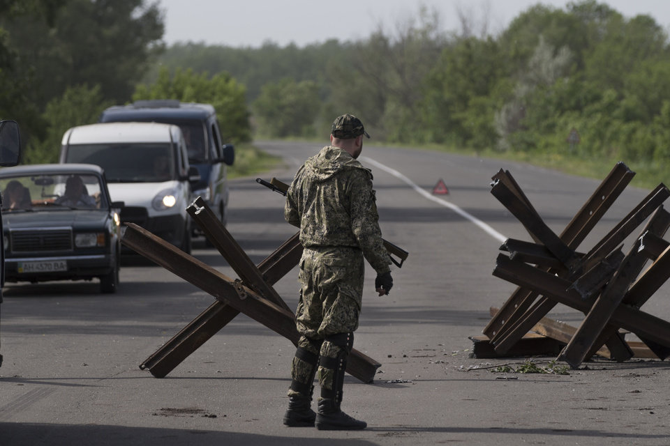 Photo - A pro-Russian armed militant guards a checkpoint blocking the major highway which links Kharkiv, outside  Slovyansk, eastern Ukraine, Monday, May 19, 2014. Lawmakers and officials from eastern Ukraine on Saturday poured criticism on the fledging central government, accusing it of ignoring legitimate grievances of the regions which have been overrun by pro-Russia militia fighting for independence. (AP Photo/Alexander Zemlianichenko)