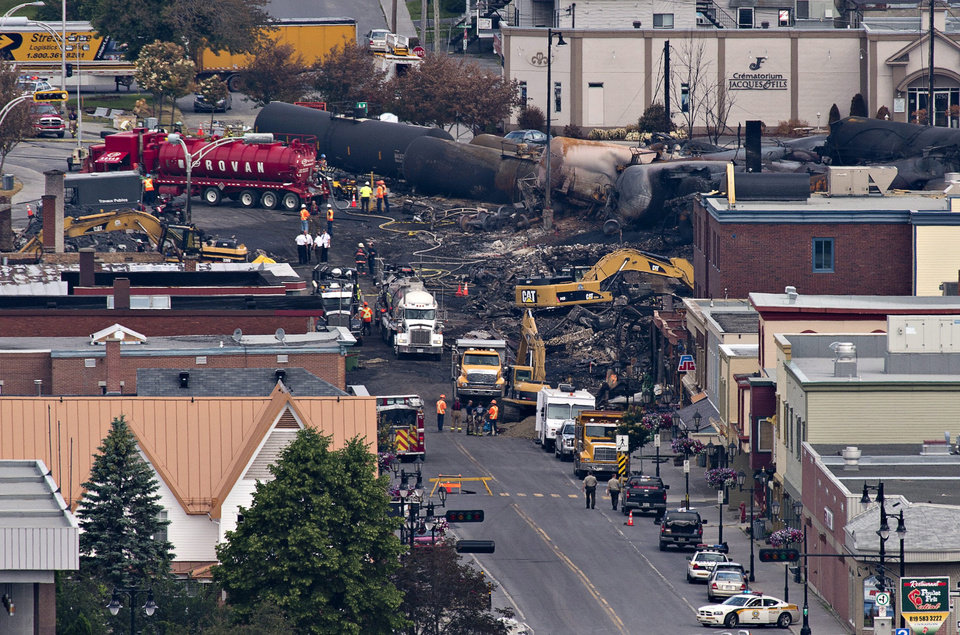 Photo - Investigators dig through the rubble for victims of Saturday's  fiery oil train derailment in Lac-Megantic, Que., Tuesday, July 9, 2013.  Thirteen dead have been found and about 40 people are still missing. (AP Photo/The Canadian Press, Jacques Boissinot)