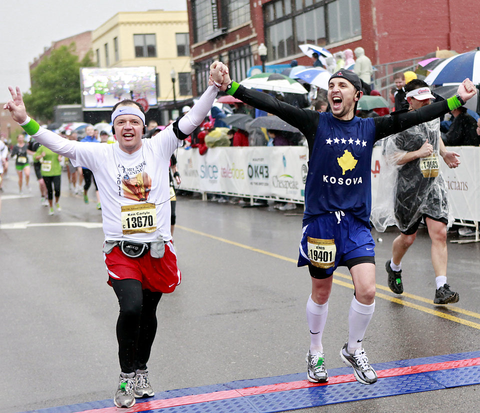 Ken Carlyle (left) and Enis Mullaliu (right) celebrate as they finish the half marathon during the 11th Annual Oklahoma City Memorial Marathon in Oklahoma City on Sunday, May 1, 2011. Photo by John Clanton, The Oklahoman