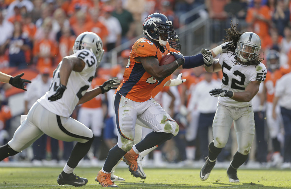 Denver Broncos running back Willis McGahee (23) runs the ball against Oakland Raiders defensive back Joselio Hanson (23) and outside linebacker Philip Wheeler (52)during the third quarter of an NFL football game, Sunday, Sept. 30, 2012, in Denver. (AP Photo/Joe Mahoney)
