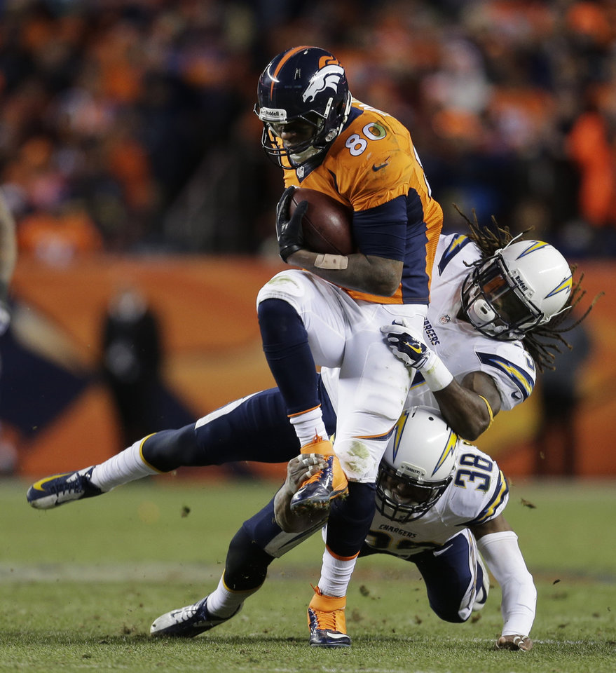 Photo - Denver Broncos tight end Julius Thomas (80) is pulled down by San Diego Chargers defensive back Jahleel Addae (37) and San Diego Chargers strong safety Marcus Gilchrist (38) in the fourth quarter of an NFL AFC division playoff football game, Sunday, Jan. 12, 2014, in Denver. (AP Photo/Joe Mahoney)