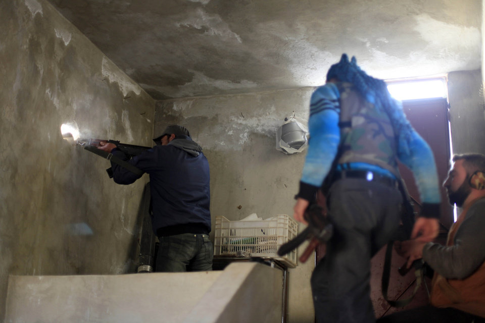 Photo -   A Syrian fighter shoots his weapon through a hole in the wall during clashes with Syrian army forces in the town of Harem on the outskirts of Idlib, Syria, Saturday, Nov. 17, 2012. (AP Photo/ Khalil Hamra)