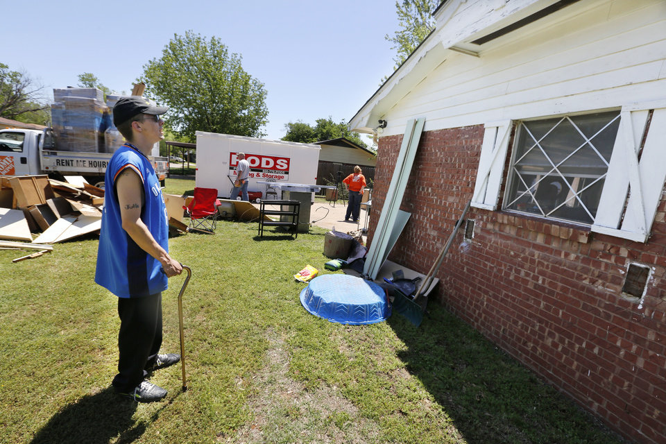 Photo - Iraq War veteran Josh Lozier looks at his home in Midwest City. Volunteers from Home Depot were refurbishing Lozier's house. Photo By Steve Gooch, The Oklahoman  Steve Gooch - The Oklahoman