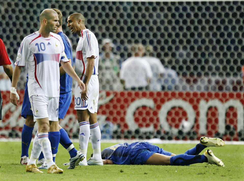 Photo -   FILE - In this July 9, 2006 file photo, France's Zineidine Zidane (10) walks past Italy's Marco Materazzi, on the ground, after he received a red card in the final of the soccer World Cup in Berlin. A 5-meter statue portraying Zidane aiming his shaven head at Italian opponent Marco Materazzi's torso has been erected in front of Paris' Centre Pompidou modern art museum. Zidane played for Real Madrid and other professional teams and helped France to victory at the 1998 World Cup. But in the 110th minute of a riveting World Cup final in 2006 against Italy, Zidane lowered his head and rammed Materazzi's chest, knocking him to the ground. (AP Photo/Luca Bruno, File)