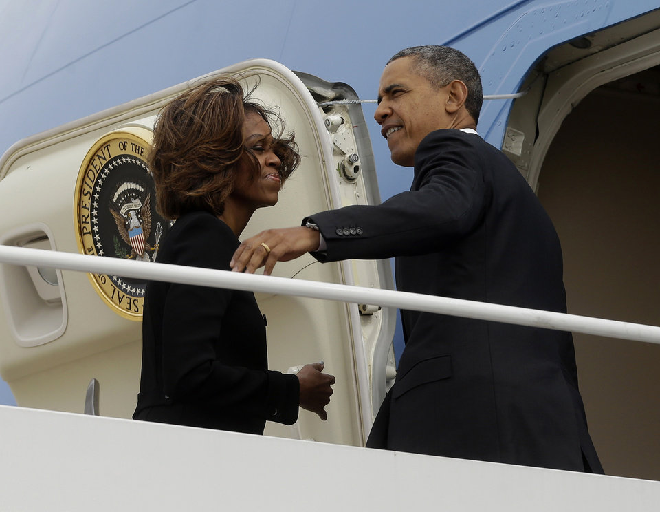 Photo - President Barack Obama and first Lady Michelle Obama prepare to board Air Force One before their departure from Andrews Air Force Base, Friday, March 7, 2014. Obama and the first lady are traveling to Miami and will visit a local high school to unveil a new initiative program to ensure more students complete the Free Application for Federal Student Aid (FAFSA), a document required by most types of financial aid such as Pell grants. (AP Photo/Pablo Martinez Monsivais)