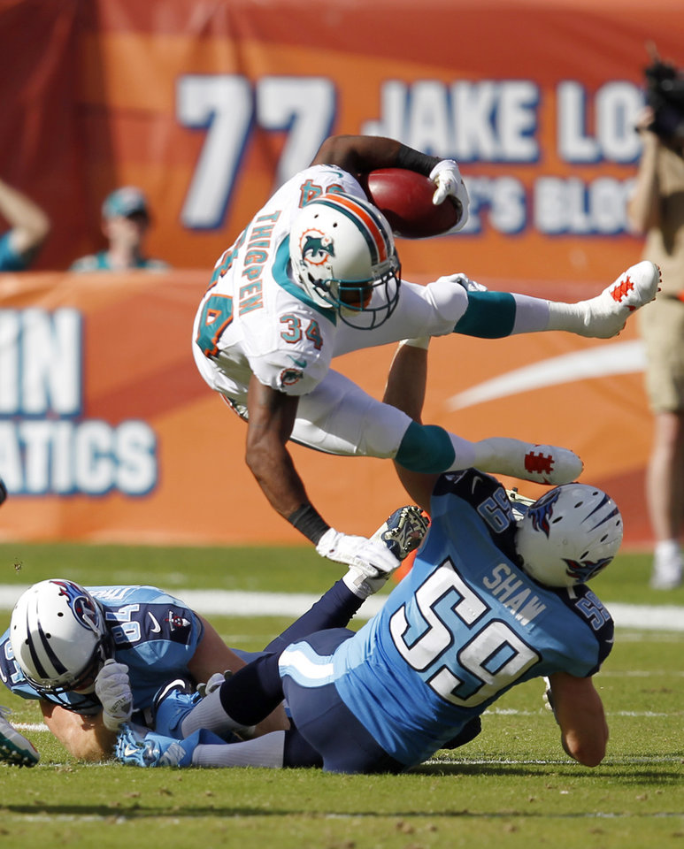 Photo -   Miami Dolphins running back Marcus Thigpen (34) is tackled on a punt return by Tennessee Titans linebacker Tim Shaw (59) and tight end Taylor Thompson (84) during the first half of an NFL football game, Sunday, Nov. 11, 2012 in Miami. AP Photo/Wilfredo Lee)
